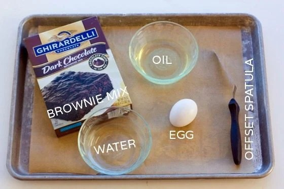 All of the brownie brittle ingredients that you need to make this recipe: brownie mix, oil, water, and an egg.