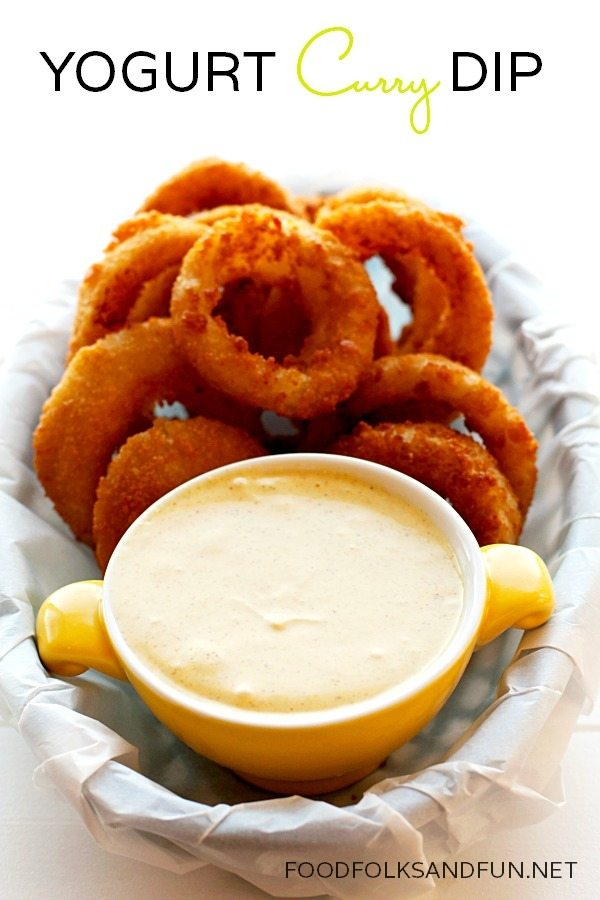 Yogurt Curry Dip in a yellow bowl inside of a basket full of onion rings.