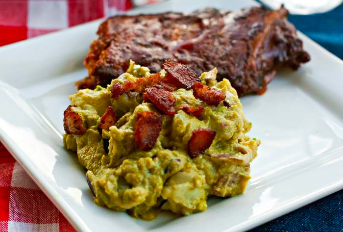 Bacon and Avocado Potato Salad on a plate with ribs in the background.