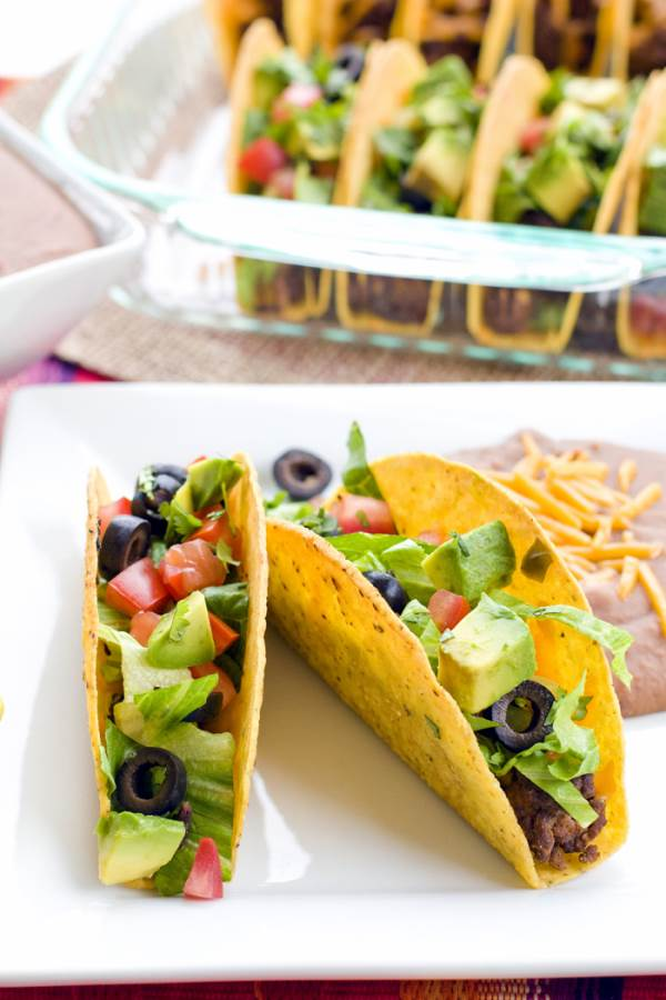 A plate of two oven tacos with a baking dish of oven tacos in the background