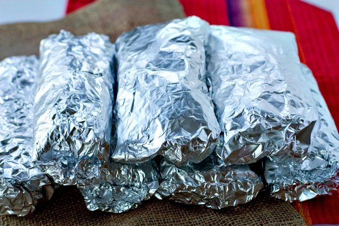 Breakfast burritos in a stack in tin foil
