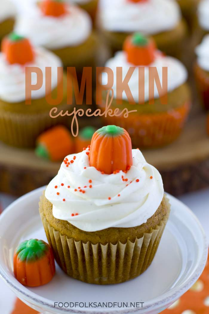 A pumpkin cupcake on a plate with more in the background and text overlay for Pinterest