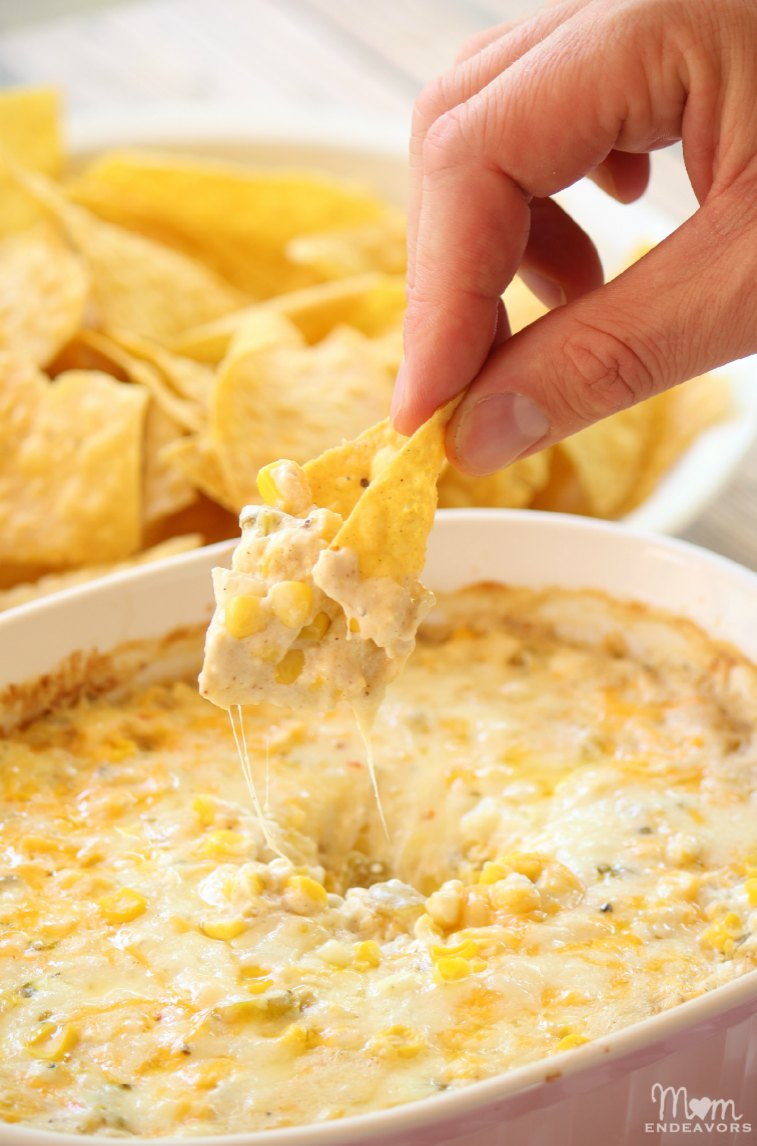 Cheesy corn dip in a bowl with chips on the side