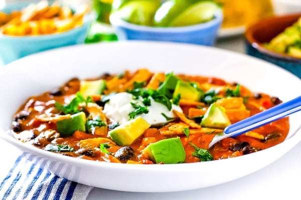 Enchilada soup in a white bowl with a blue spoon in it.