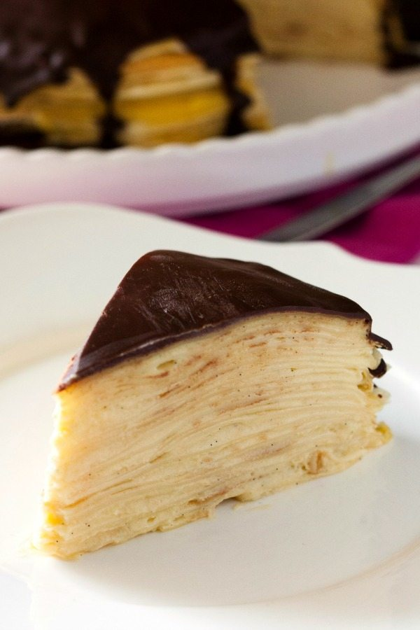 A slice of Boston cream pie crepe cake on a white plate.