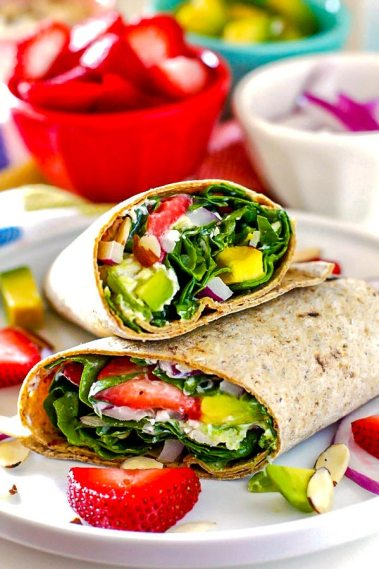 A spinach wrap cut in half and stacked on top of each other.