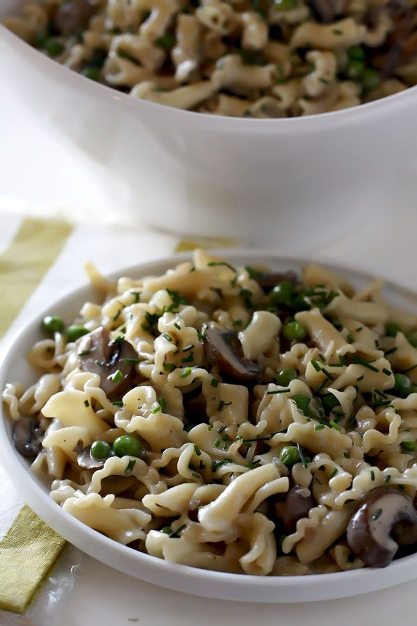 Pasta with mushrooms on a white plate and in a white serving bowl.