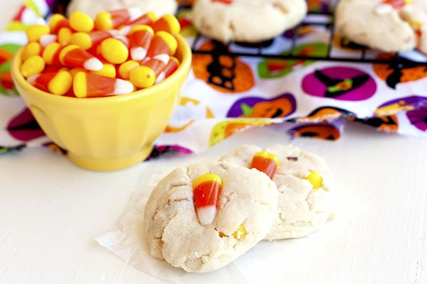 Two sweet and salty candy corn cookies with a bowl of candy corn and more cookies on a wire rack in the background