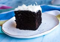 Chocolate cake on a plate with white 7 minute frosting.