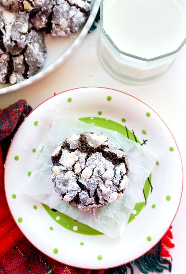 A chocolate crinkle cookie with hazelnuts on a plate