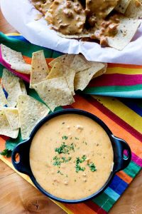 Chile Con Queso in a small serving bowl with a side of chips