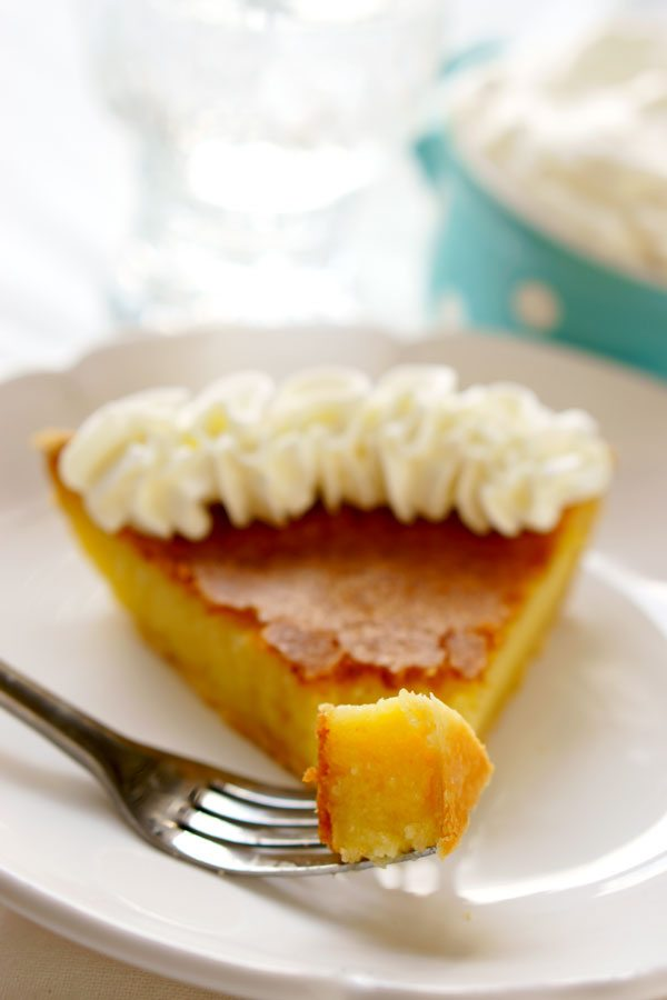 A fork taking a piece out of a slice of buttermilk pie on a white plate.