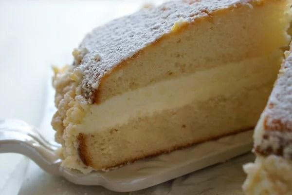 A close-up of a slice of Copycat Olive Garden Lemon Cake on a cake