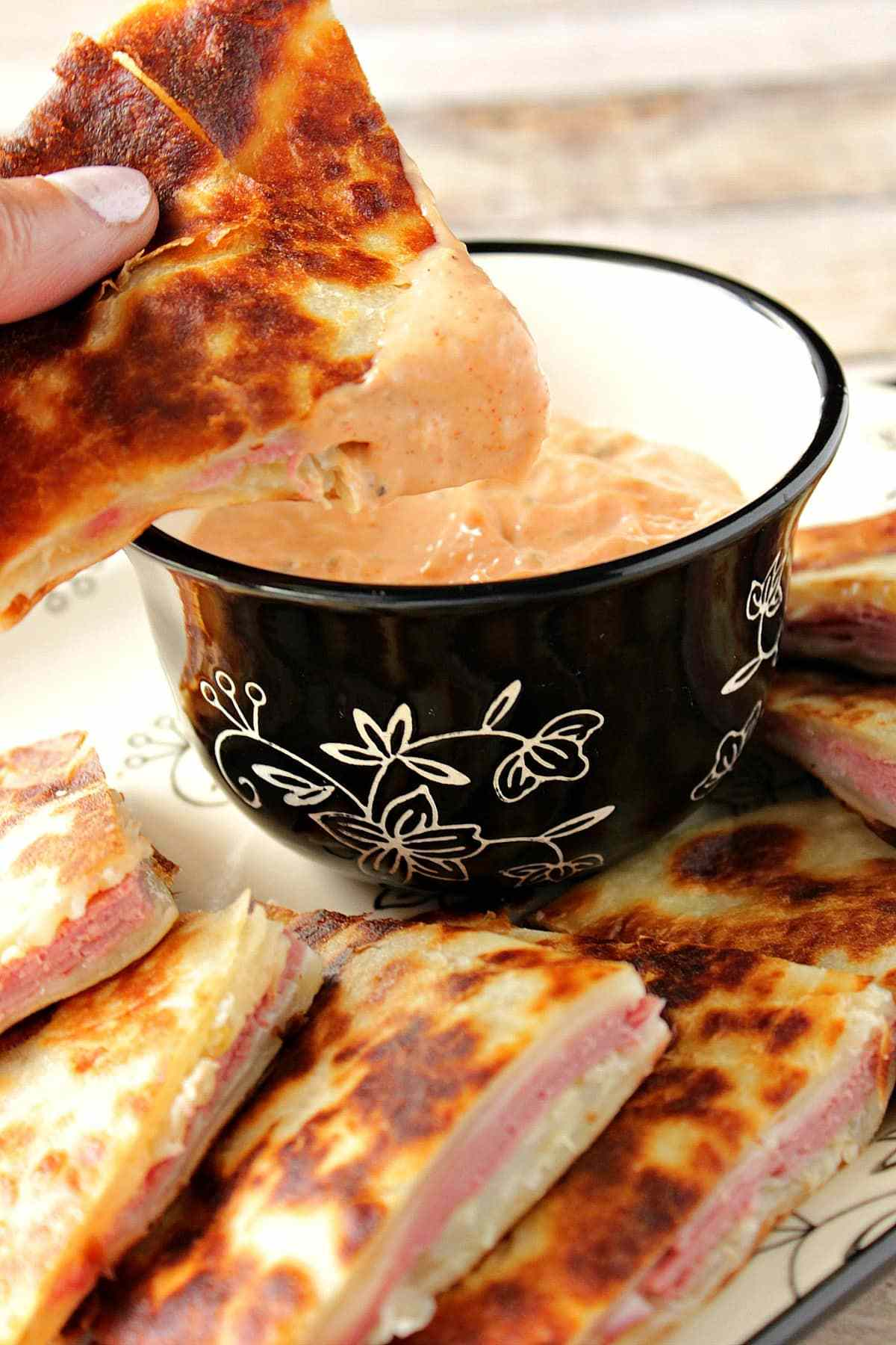Reuben quesadilla triangles on a serving platter with a bowl of dipping sauce