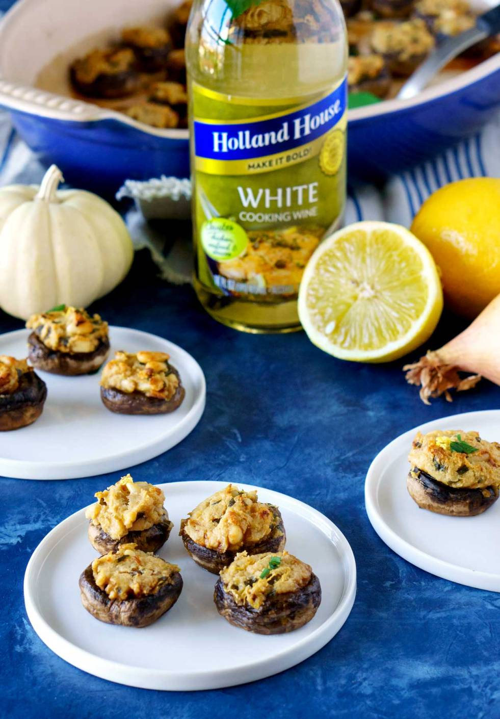 Stuffed mushrooms on white appetizer plates with a lemon and shallop in the background.