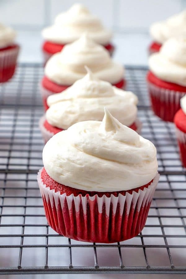 Red velvet cupcakes on a wire rack.