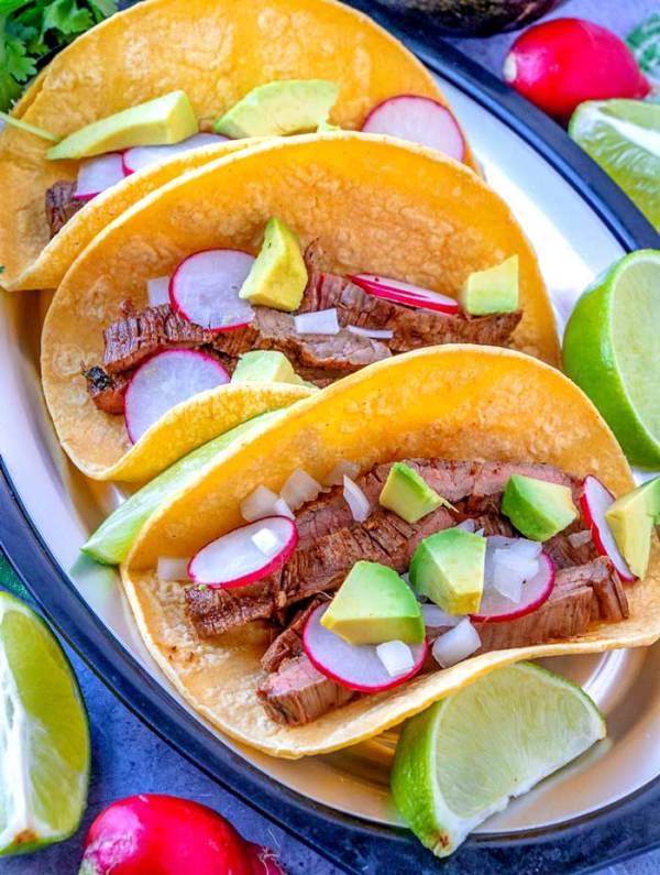 3 Carne Asada Street Tacos on a plate with radishes, chopped onions, and avocado.