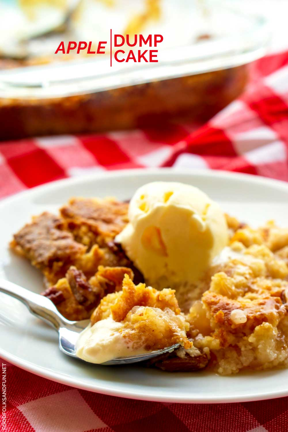 Dump cake on a white plate with a spoon digging into it.