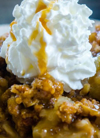 A close up picture of apple crisp with whipped cream and caramel sauce.