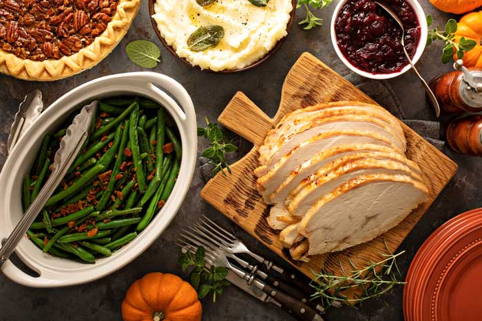 An overhead picture of a Thanksgiving table with sliced roast turkey, green beans, cranberry sauce, and mashed potatoes.