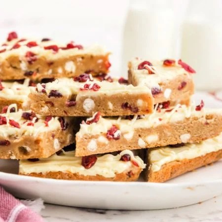 Sliced cranberry bliss bars stacked on top of each other on a white platter.
