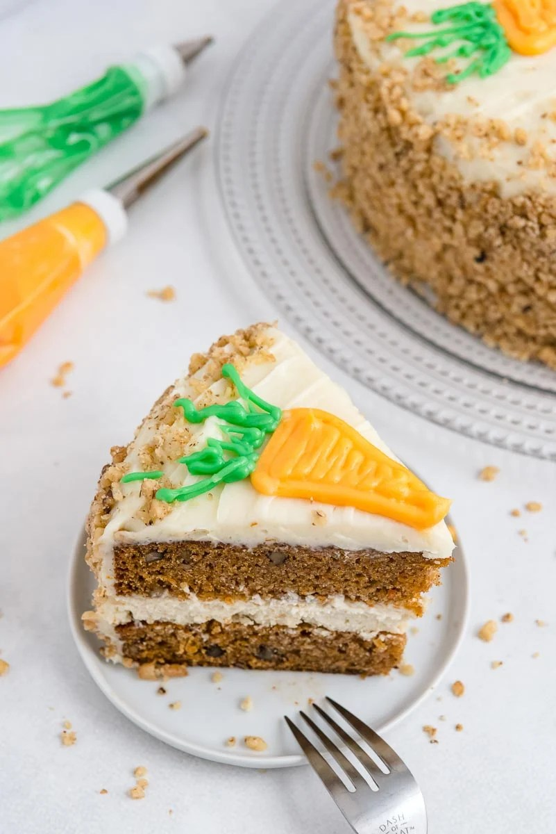 A slice of Cheesecake Factory Carrot Cake Copycat on a white plate.
