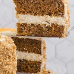 A slice of Cheesecake Factory Carrot Cake being taken from the whole cake.