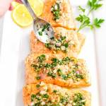 An overhead picture of baked salmon on a plate that is having lemon vinaigrette spooned over it.