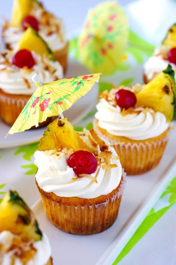 Pineapple and coconut frosting garnished with paper drink umbrellas, coconut, pineapple, and cherries.