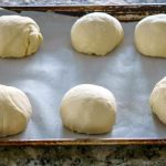 Place the dough balls on a greased piece of parchment and over and rest the dough.