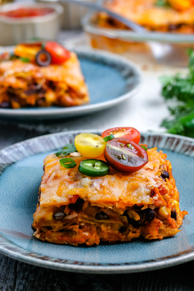 A slice of stacked chicken enchilada casserole on a blue plate.