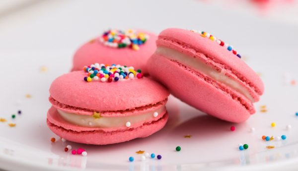Three pink macarons on a white plate.