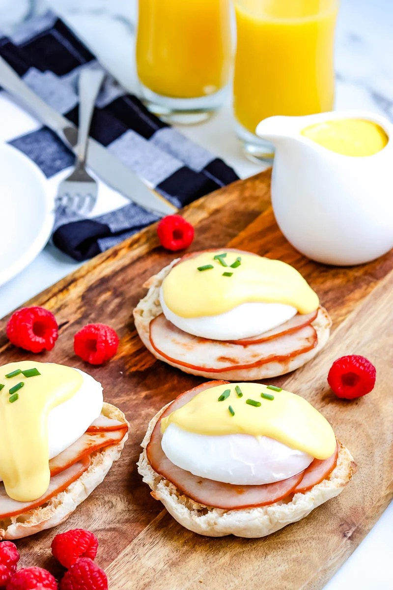 The finished Eggs Benedict on a wood platter with raspberries sprinkled around.