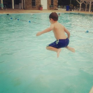 young boy jump in the pool