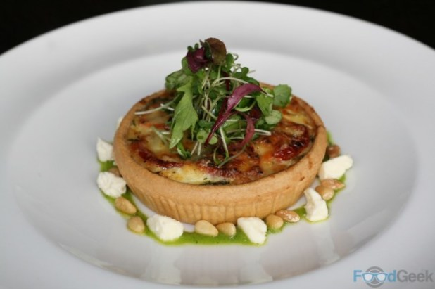 Warm caramelised onion and tomato quiche, rocket pesto, Leagram's Lancashire curd cheese, pine nuts