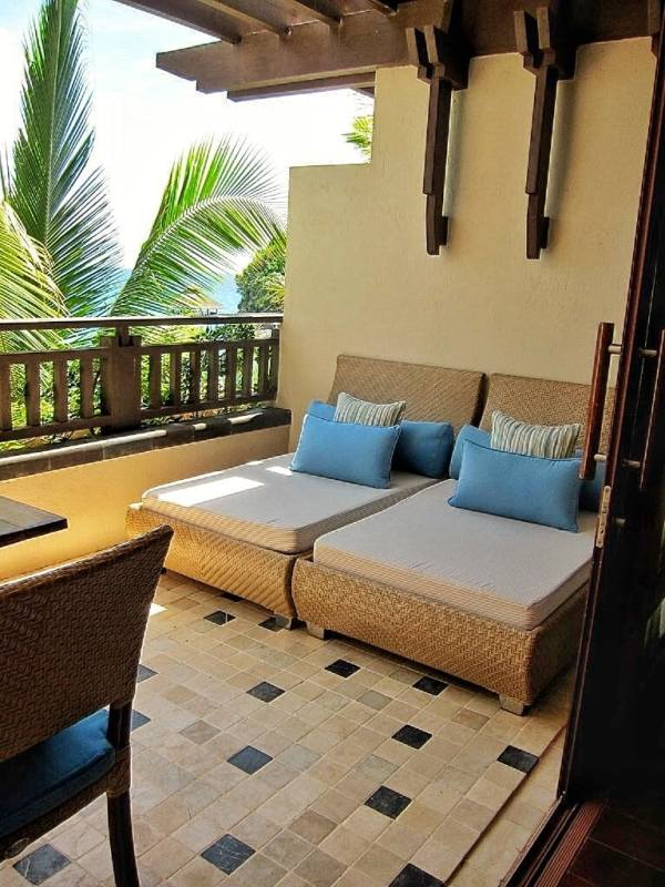 Balcony with a table and day beds.