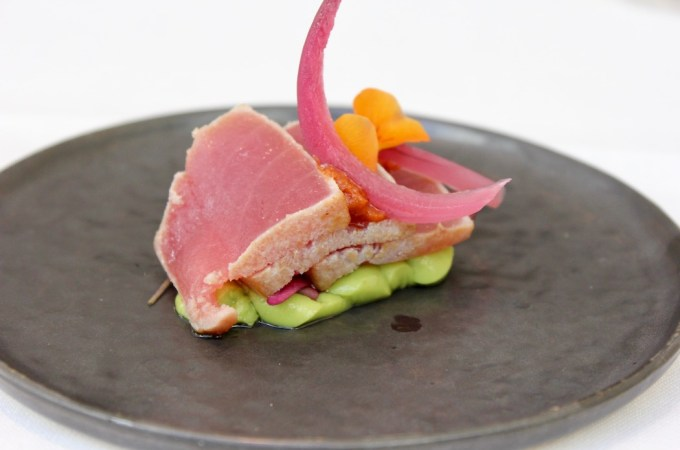 Tuna tatami with pickled red onions on an avocado cream.