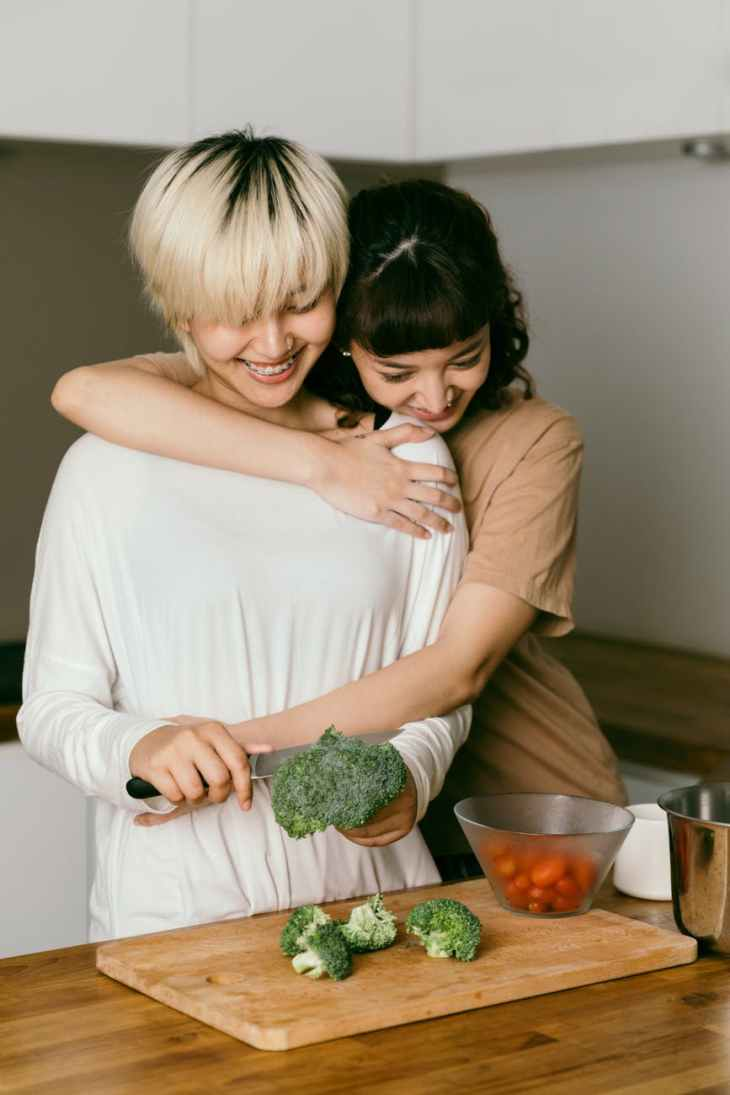 cheerful lesbian couple hugging and cooking dinner together