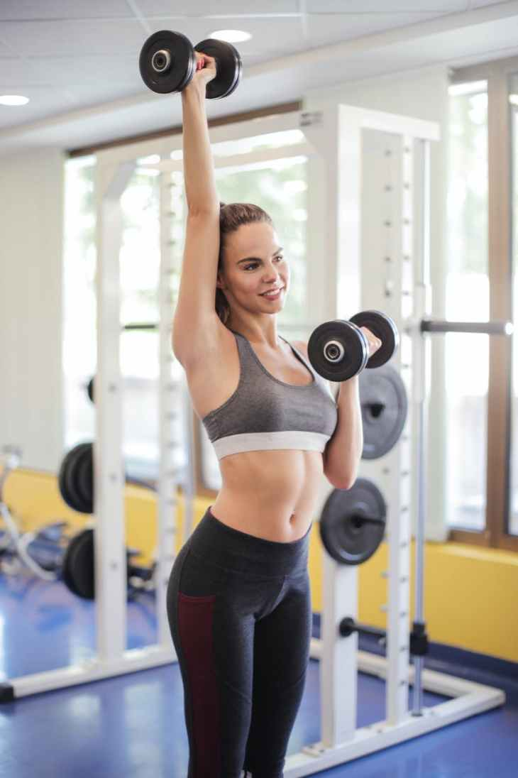 photo of woman using dumbbells