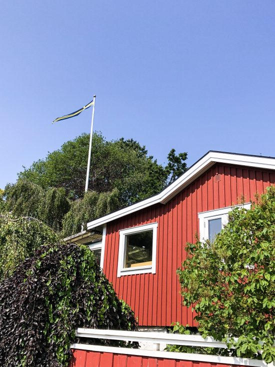 Red house and Swedish Flag on Branno Island, 10 Things To Do and See in Gothenburg - www.foodnerd4life.com