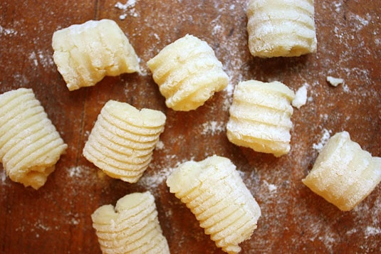 Two kinds of gnocchi side by side: rolled on a special board, and rolled on a fork.