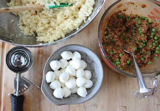 Making Arancine con Ragù: Prepare your workspace: set the bowl of cooked rice, the meat sauce and the cheese cubes in front of you, assembly-line style.