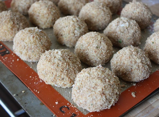 Making Arancine con Ragù: rice balls covered in bread crumbs, before frying