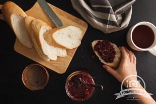 bread and raspberries jam on black background. Overhead view