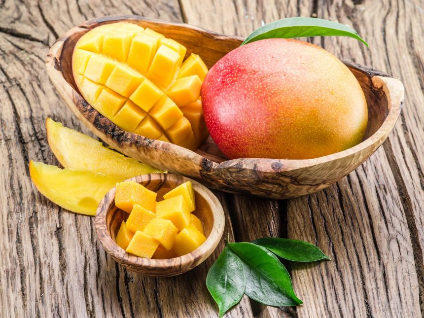 mango and cut mango in wooden bowl on table