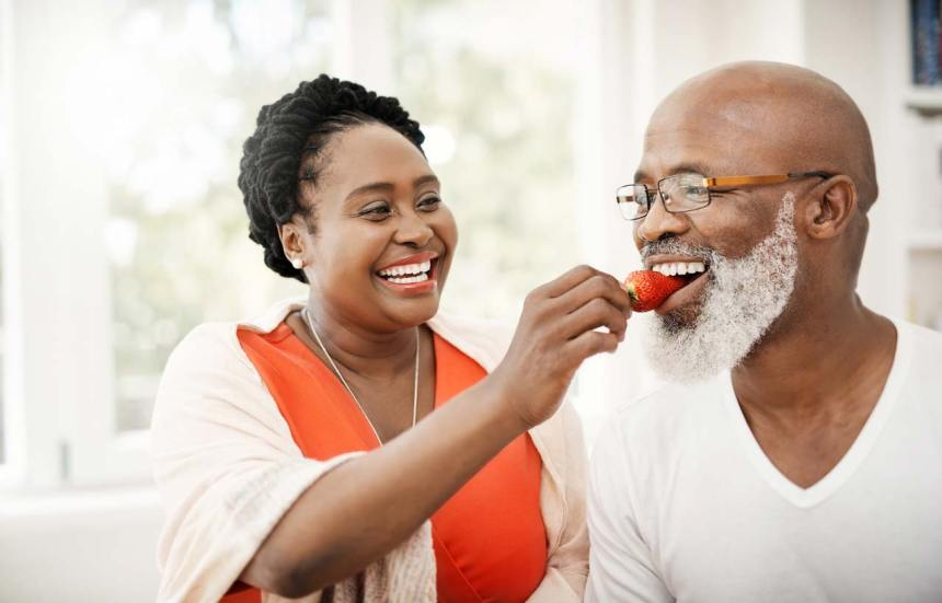 woman feeding man strawberry