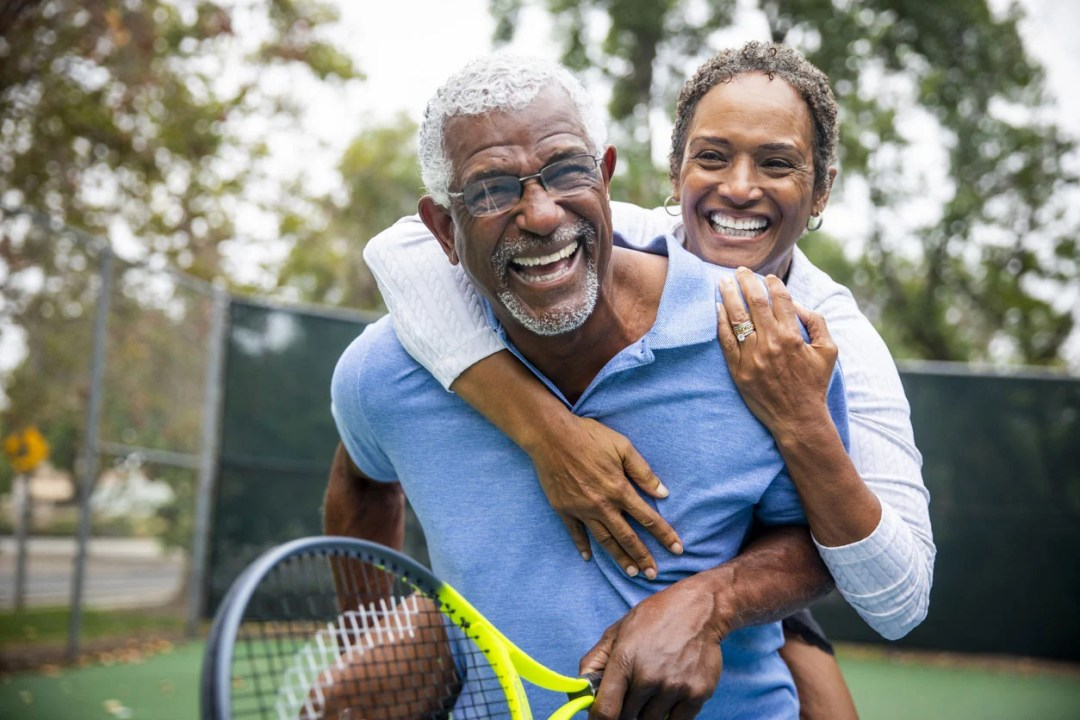 年長的夫婦在網球場上背piggy式