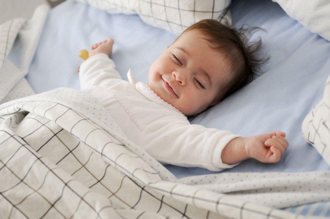 如何像這個微笑的女嬰在床上那樣睡個好覺