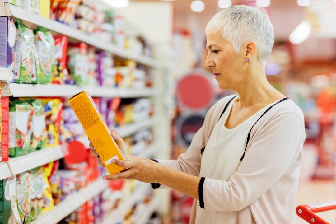 一個女人看著可能在尋找自然風味的盒子上的成分