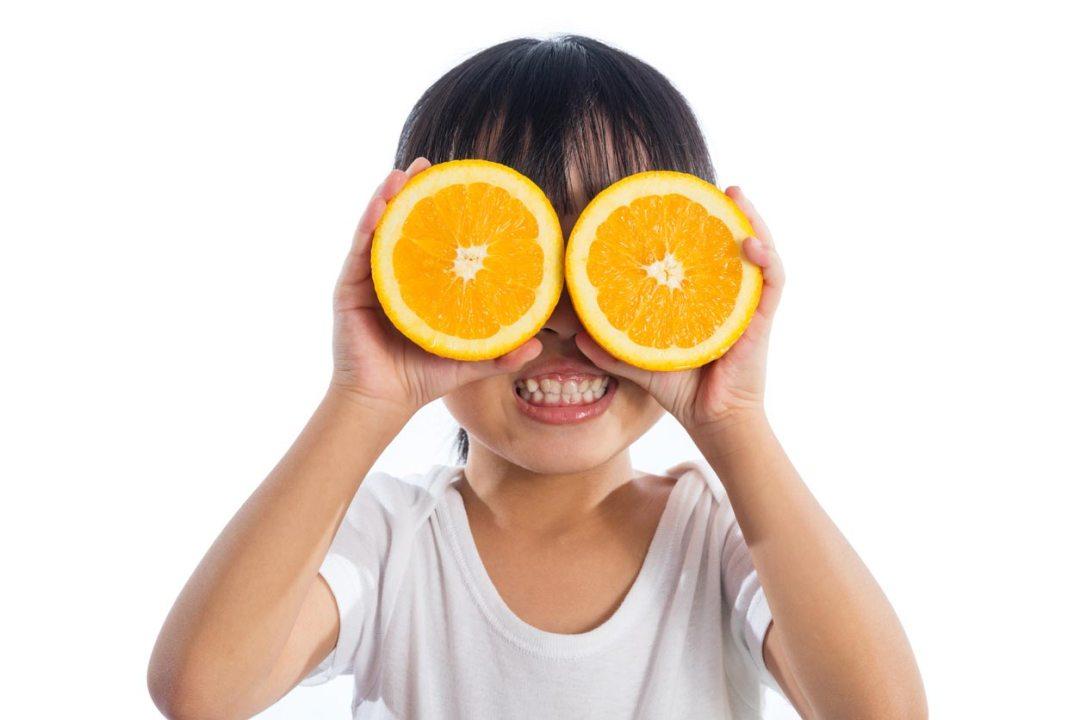 使用桔子作為眼鏡的小女孩